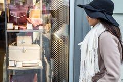 Giovane donna che esamina la finestra del negozio Immagine Stock