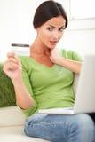 Giovane donna che esamina sorpresa la carta di credito Immagine Stock