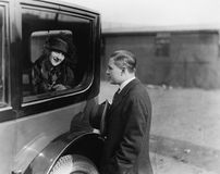 Giovane donna che esamina un uomo attraverso una finestra di automobile (tutte le persone rappresentate non sono vivente più lung Fotografia Stock