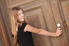 Giovane donna che esamina una vecchia porta immagine stock libera da diritti