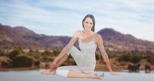 Giovane donna che esegue yoga con le montagne nel fondo Immagini Stock