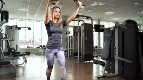 Giovane donna che esercita allenamento facendo uso delle cinghie TRX di forma fisica nella palestra stock footage