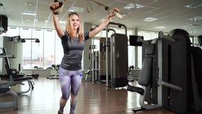 Giovane donna che esercita allenamento facendo uso delle cinghie TRX di forma fisica nella palestra video d archivio
