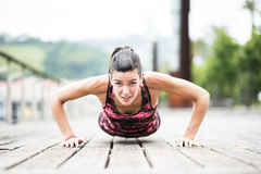 Giovane donna che esercita Spinta-UPS sul pavimento di legno. Fotografie Stock