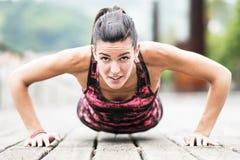 Giovane donna che esercita Spinta-UPS sul pavimento di legno. Fotografia Stock Libera da Diritti