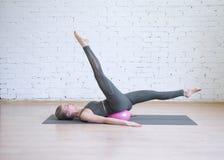 Giovane donna che fa allenamento con la piccola palla rosa di forma fisica, esercizio dei pilates di vantaggi Dell'interno, fondo fotografie stock libere da diritti