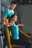 Giovane donna che fa allenamento delle spalle con le teste di legno in una palestra Fotografia Stock