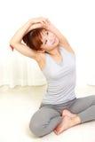Giovane donna che fa allungamento della spalla di auto Fotografia Stock
