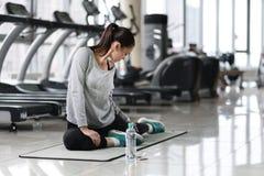 Giovane donna che fa allungamento dopo l'allenamento in una palestra Immagini Stock Libere da Diritti