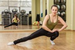 Giovane donna che fa allungamento nella classe di forma fisica Fotografia Stock Libera da Diritti