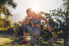 Giovane donna che fa allungando allenamento ad un parco Fotografie Stock