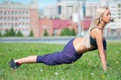 Giovane donna che fa allungando esercitazione su erba Immagini Stock Libere da Diritti