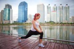 Giovane donna che fa allungando esercizio Immagine Stock