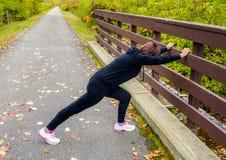 Giovane donna che fa allungando esercizio su un percorso pavimentato Fotografie Stock