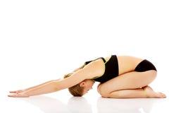 Giovane donna che fa allungando esercizio sul pavimento Fotografie Stock