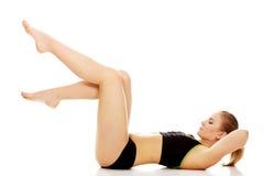 Giovane donna che fa allungando esercizio sul pavimento Fotografia Stock Libera da Diritti