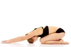 Giovane donna che fa allungando esercizio sul pavimento Immagine Stock