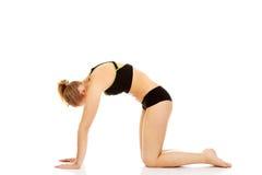 Giovane donna che fa allungando esercizio sul pavimento Fotografie Stock Libere da Diritti