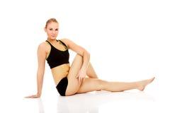Giovane donna che fa allungando esercizio sul pavimento Fotografia Stock