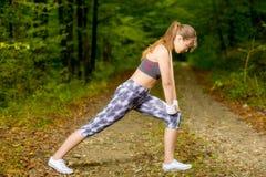 Giovane donna che fa allungando esercizio sulla foresta della strada Immagini Stock