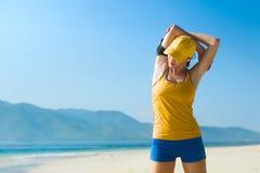Giovane donna che fa allungando esercizio sulla spiaggia Fotografie Stock Libere da Diritti