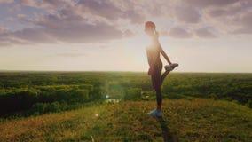 Giovane donna che fa allungando esercizio in un bello posto epico al tramonto Bello abbagliamento dal sole, la cima della a Fotografia Stock