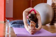 Giovane donna che fa allungando gli esercizi delle gambe ed indietro su una stuoia porpora di forma fisica Il concetto di forma f Immagini Stock