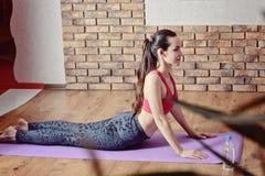 Giovane donna che fa allungando gli esercizi delle gambe ed indietro su una stuoia porpora di forma fisica Il concetto di forma f Immagini Stock Libere da Diritti