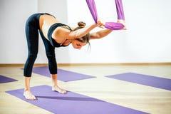 Giovane donna che fa allungando gli esercizi facendo uso dell'amaca Yoga aerea Immagine Stock