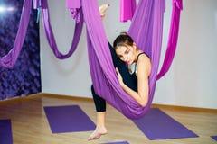 Giovane donna che fa allungando gli esercizi facendo uso dell'amaca Yoga aerea Fotografia Stock Libera da Diritti