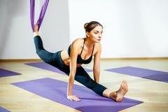 Giovane donna che fa allungando gli esercizi facendo uso dell'amaca Yoga aerea Fotografia Stock