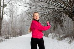 Giovane donna che fa allungando gli esercizi nell'inverno Immagini Stock Libere da Diritti