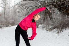 Giovane donna che fa allungando gli esercizi nell'inverno Fotografia Stock