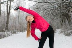 Giovane donna che fa allungando gli esercizi nell'inverno Immagine Stock