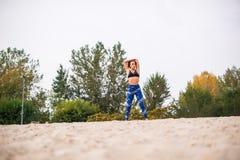 Giovane donna che fa allungando gli esercizi nella natura Immagini Stock