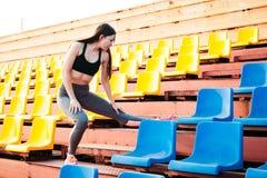 Giovane donna che fa allungando gli esercizi sulla tribuna dello stadio immagini stock libere da diritti