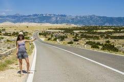 Giovane donna che fa auto-stop lungo la strada vuota Fotografie Stock