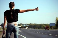 Giovane donna che fa auto-stop sulla strada Fotografia Stock