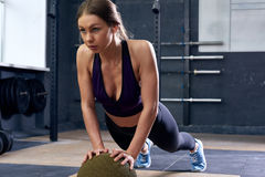 Giovane donna che fa esercizio della plancia sulla palla Immagini Stock