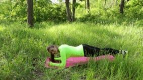 Giovane donna che fa esercizio della plancia sulla stuoia nello sguardo del parco a sorridere della macchina fotografica stock footage