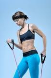 Giovane donna che fa esercizio di allenamento con l'allungamento dell'estensore Fotografia Stock Libera da Diritti