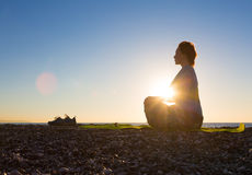 Giovane donna che fa esercizio di yoga sulla spiaggia tropicale all'alba immagine stock libera da diritti