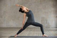 Giovane donna che fa esercizio inverso del guerriero Fotografia Stock