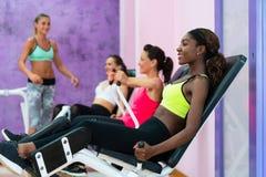 Giovane donna che fa esercizio per le gambe mentre assistendo alla classe del gruppo Fotografie Stock