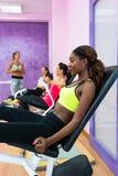 Giovane donna che fa esercizio per le gambe mentre assistendo alla classe del gruppo Immagine Stock Libera da Diritti