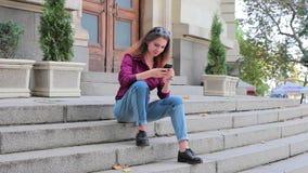 Giovane donna che fa foto mobile sulla via che si siede sui punti video d archivio