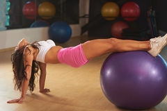 Giovane donna che fa gli allungamenti nel club di forma fisica Immagine Stock