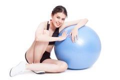 Giovane donna che fa gli esercizi con la palla di forma fisica fotografia stock libera da diritti