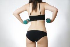 Giovane donna che fa gli esercizi con le teste di legno Fotografie Stock Libere da Diritti