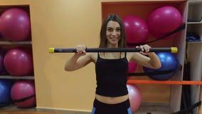 Giovane donna che fa gli esercizi dei pilates con il bastone relativo alla ginnastica video d archivio